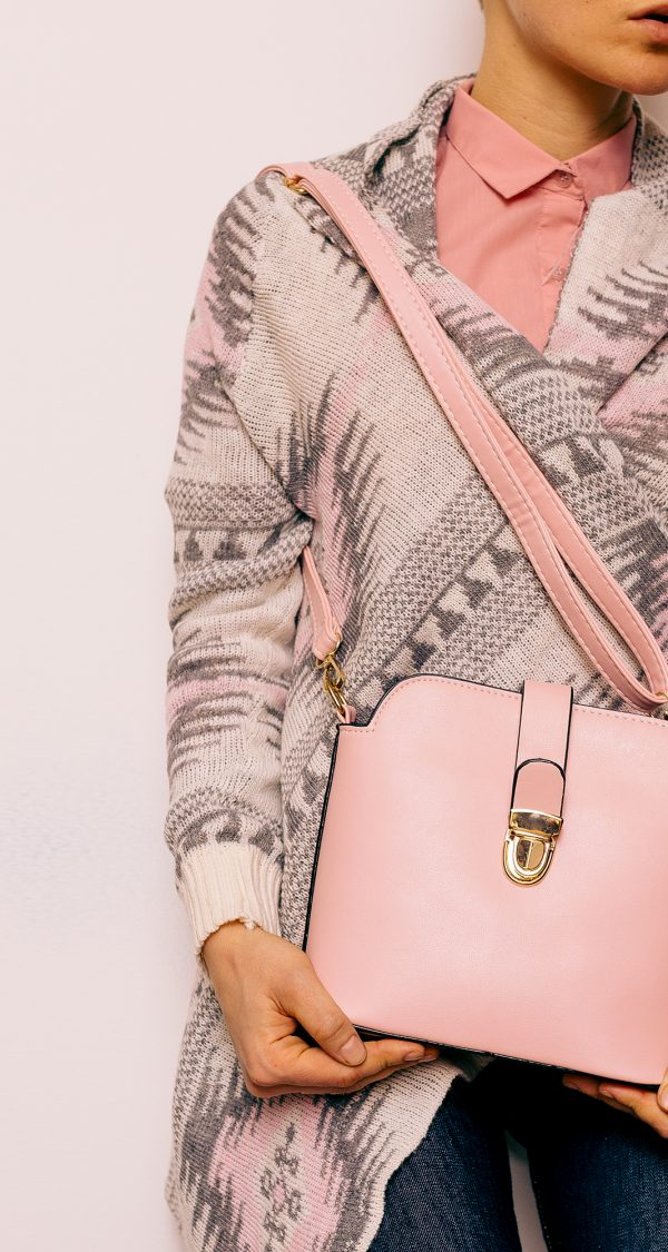 Girl in sweater ornaments and fashion accessories. Bag and stylish blue jeans